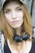 Stock Photo of Portrait of a young woman with cap and headphones around her neck
