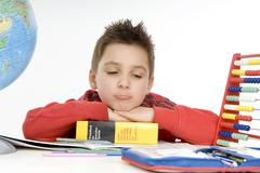 7 year-old schoolboy sitting at his desk, not concentrating Stock Photos