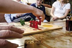 Senior citizens playing ludo with over-sized game pieces at an old-age home Stock Photos