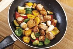 Colourful pan-fried meat with vegetables, capsicums, zucchinis and scallions Stock Photos