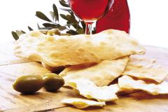 Stock Photo of mother-in-laws' tongues, lingue di suocera, flatbread with olives and red wi