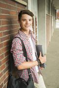 Smiling teenage boy leaning against brick wall - stock photo