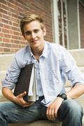 Smiling young man holding file folder - stock photo