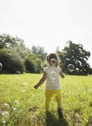 Little girl walking on a meadow, back view Stock Photos