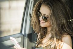 Portrait of smiling teenage girl with sunglasses sitting in a car watching her Stock Photos