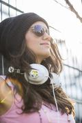 Portrait of smiling teenage girl with headphones wearing sunglasses and wool cap Stock Photos