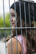 Profile of smiling teenage girl behind a fence wearing wool cap Stock Photos