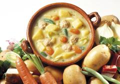 Bowl of potato soup prepared with carrots, beans and meatballs Stock Photos