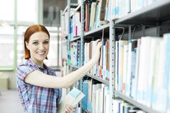 Stock Photo of Portrait of student in a university library taking book from shelf