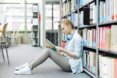 Student in a university library sitting on floor reading book Stock Photos