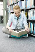 Student in a university library sitting on floor reading book - stock photo