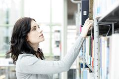 Stock Photo of Student in a university library taking book from shelf