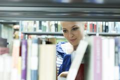 Student in a university library reading book at shelf - stock photo