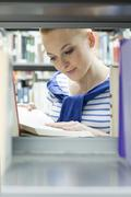 Student in a university library reading book at shelf Stock Photos