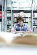 Student in a university library reading - stock photo