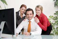 three happy businesspeople at the office - stock photo