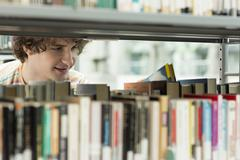Student in a university library taking book from shelf - stock photo