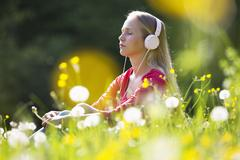 Portrait of teenage girl with headphones hearing music on a flower meadow - stock photo
