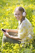 Portrait of smiling teenage girl with headphones hearing music on a flower - stock photo