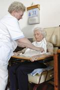 caretaker aiding a pensioner sitting in a wheelchair at a nursing home - stock photo
