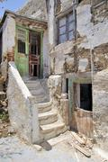 Old house with a crumbling facade, stairway and weathered paint on the door - stock photo