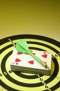 Stock Photo of dart and playing cards on dart board
