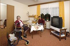 room in an old-age home, nursing home, senior being visited by her grandson - stock photo