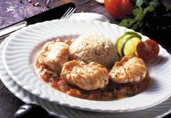 fried devilfish filets on tomato sauce with rice - stock photo