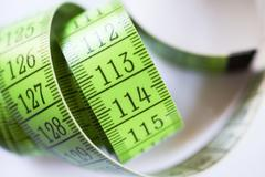 green measuring tape, tape measure - stock photo