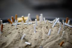 Cigarettes butt in sand ashtray Stock Photos