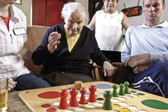 nurses and residents of an old-age home or nursing home playing board games i - stock photo
