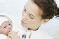 young mother, 22 years, with daughter, six weeks old, outdoors - stock photo