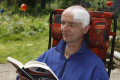 Man, 45, with an adhesive bandage on his head, sitting in a garden chair read Stock Photos