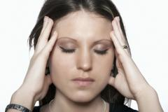 stressed young woman holding her temples - stock photo