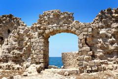 Stock Photo of the acre surrounding wall gate with small view of the mediterranean sea water