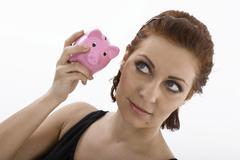Woman listening to a piggy bank Stock Photos