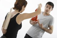 woman holding a pair of red panties accusingly in front of a man - stock photo