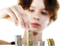 young woman stacking coins - stock photo