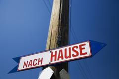 guidepost, sign reading nach hause, this way home - stock photo