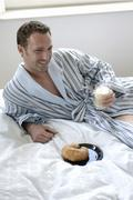31-year-old man wearing a dressing gown, bathrobe, eating breakfast in bed Stock Photos