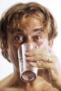 Shirtless man drinking a glass of water Kuvituskuvat