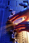 Hands of a sound engineer adjusting the regulators of a professional mixer un Stock Photos