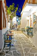 Greek chairs and tables standing on mosaic-like painted paving stones in an a Stock Photos