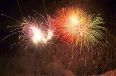 fireworks over a snow-covered spruce forest - stock photo