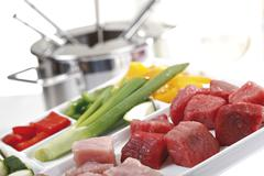 Ingredients for meat fondue, meat cubes, capsicums and scallions Stock Photos