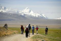Trekking group hiking towards snow covered mountains near old tingri tibet ch Kuvituskuvat