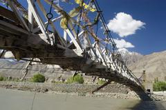 Swing bridge with prayer flags over the indus river, ladakh, jammu and kashmi Stock Photos