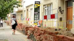 repair the urban street with buildings - grit, bricks - pavement - people walk - stock footage