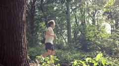 Young man exercising in the sunny forest Stock Footage