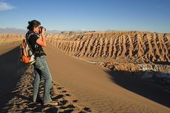 Woman with a camera on a sand dune in the moon valley (valle de la luna), ata Stock Photos